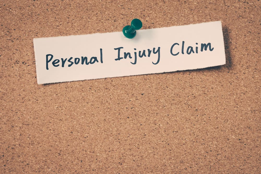 "a corkboard with a piece of paper with ""personal injury claim"" tacked to it"