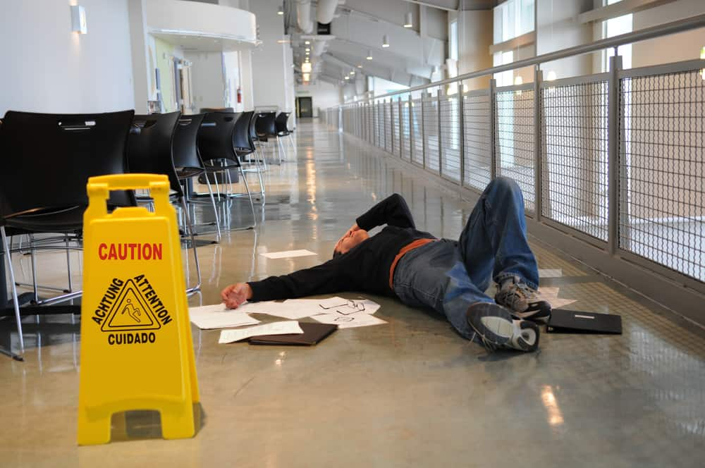 man lying on ground after slipping next to wet floor sign