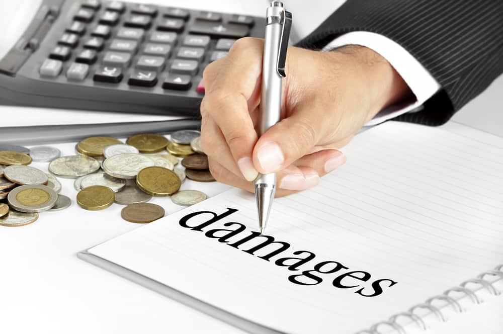 person writing damages on paper next to stack of money