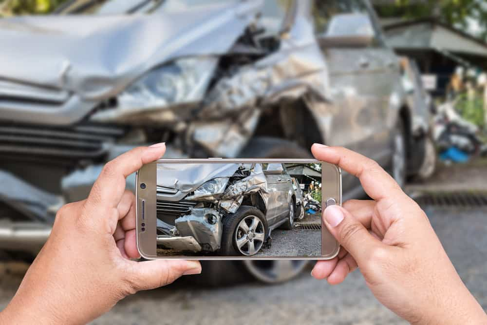image of phone camera taking photo of totaled car