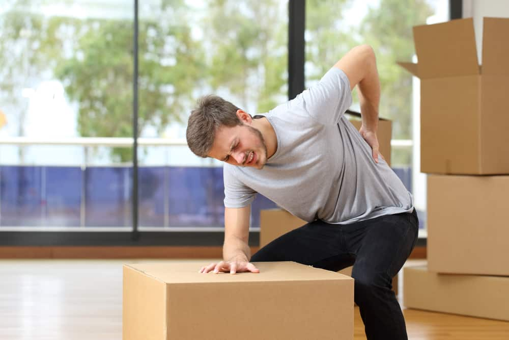 man holding back after lifting heavy boxes