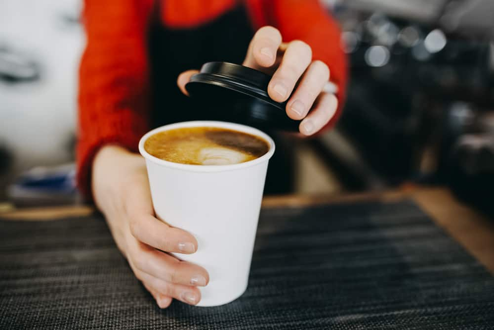 barista about to put lid on hot cup of coffee