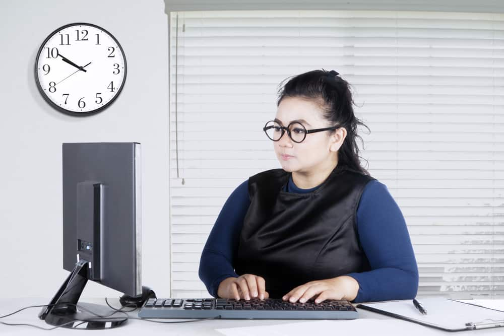 woman with glasses sitting at desk using computer