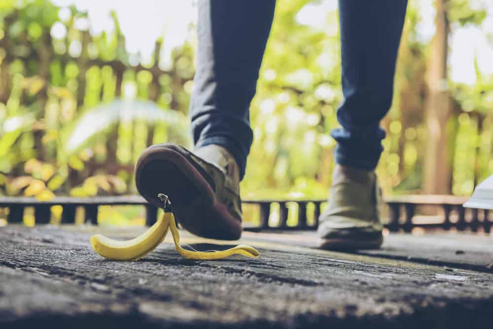 close up of a person's foot about to slip and fall on a banana