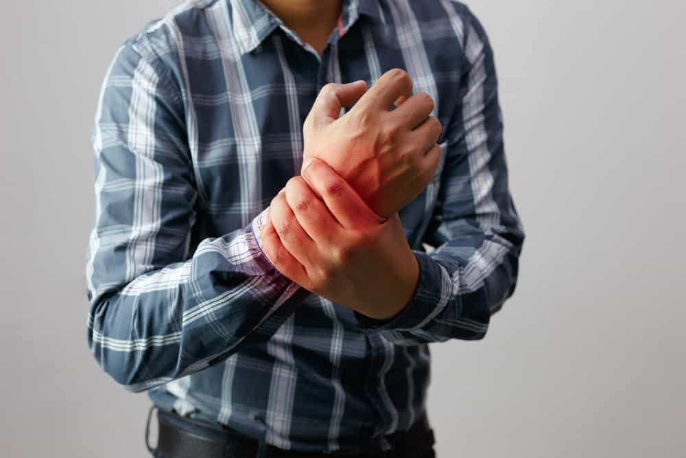 Man holding his arm in pain from arthritis