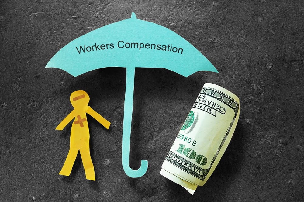 Cut out off person with workers' compensation umbrella and $100 bill