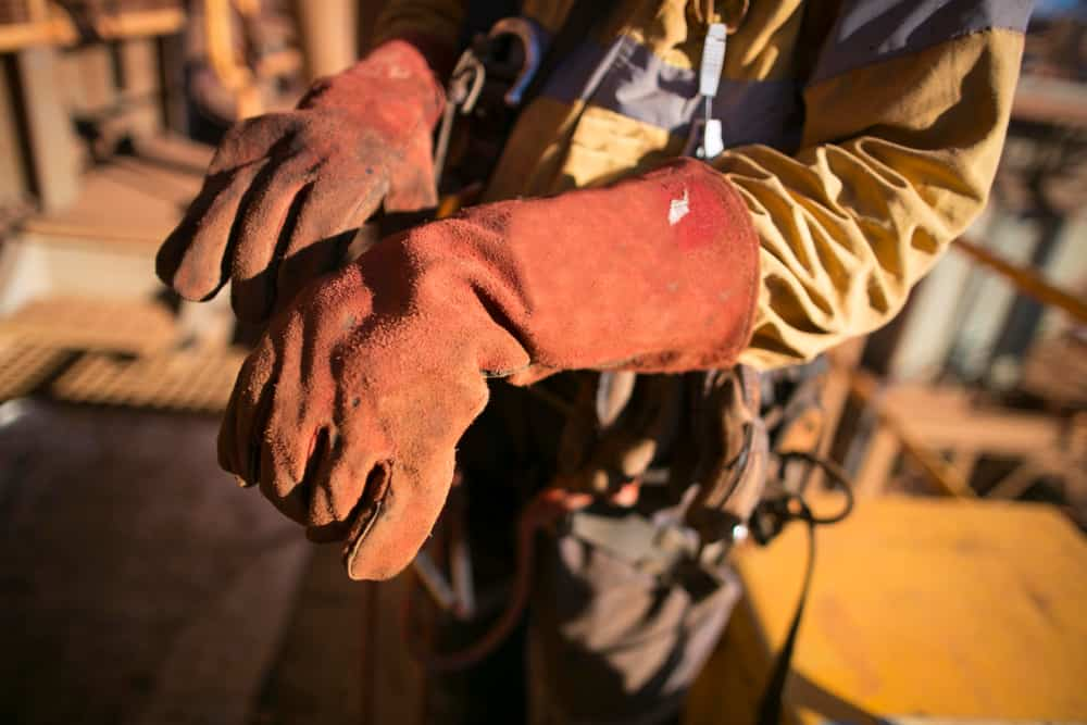 Male rope access worker welder hand preparing, wearing industry heavy duty welding glove protection prior to commencing hot work on construction site
